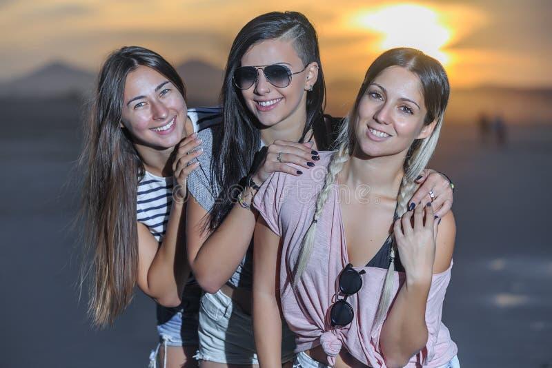 Nöjda unga kvinnor som omfamnar på stranden royaltyfri foto