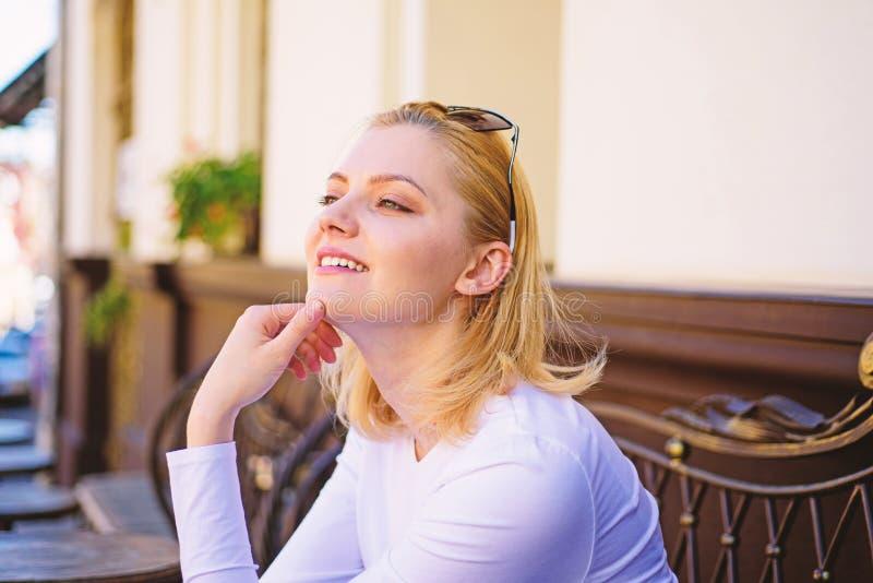Nöje på hennes mening Blont drömlikt för kvinna le framsidan utomhus och att bygga defocused bakgrund Vad gör flickadröm royaltyfria foton