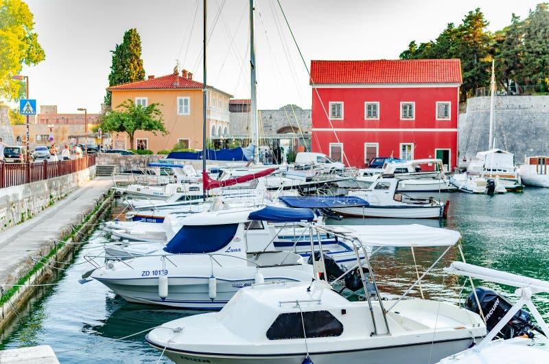 Nöjefartyg och fiskebåtar på pir i Fosa skäller i brunnsortstaden av Zadar i Kroatien fotografering för bildbyråer