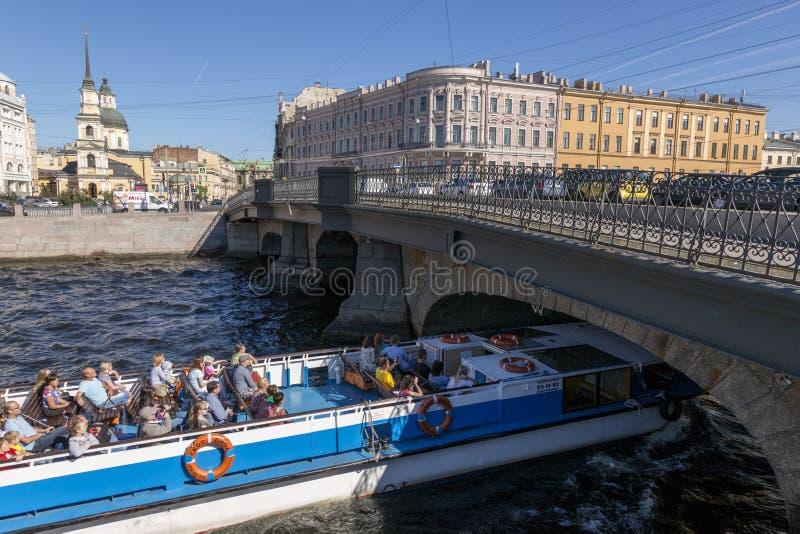 Nöjefartyget seglar under den Belinsky bron på den Fontanka floden i St Petersburg arkivbilder