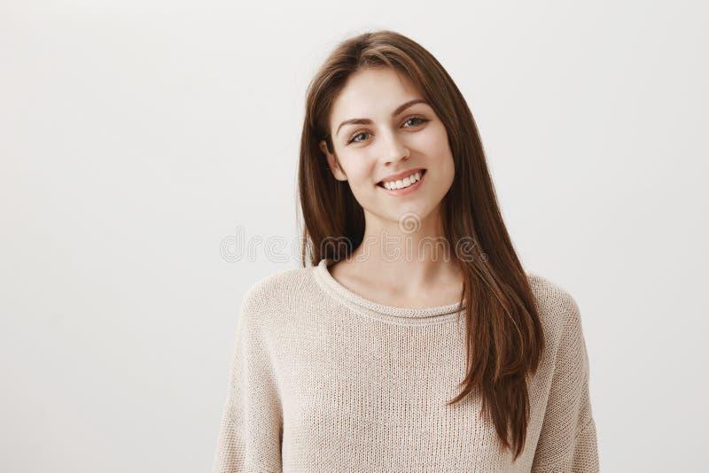 Nöjt att hjälpa dig Stående av det artiga snygga kontorsassistentanseendet i varm tröja och att le i huvudsak fotografering för bildbyråer