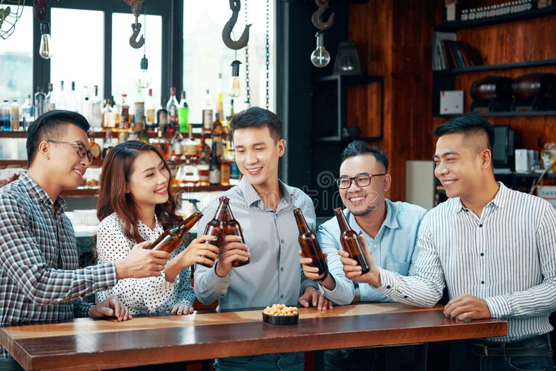 Nöjt folk som dricker öl i stång royaltyfri fotografi