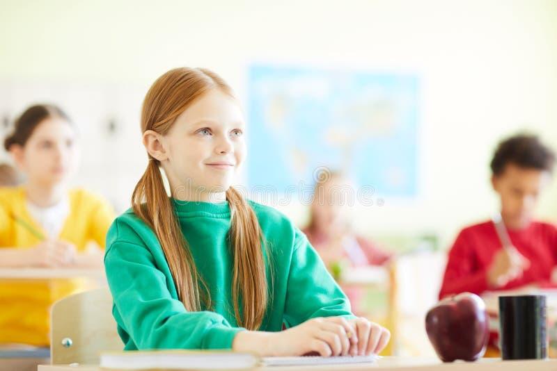 Nöjt rödhårig manflickasammanträde på skrivbordet i skola arkivbilder