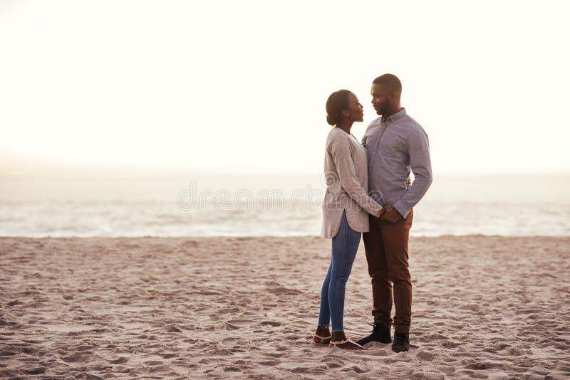 Nöjt ungt afrikanskt paranseende på en strand på skymning royaltyfri bild