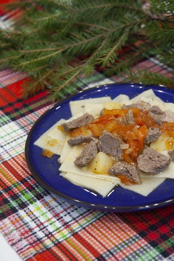 Nötkött eller lamm med fyrkant-formad pasta med potatisar och paprika Uzbekisk traditionell kokkonst - Shilpildok arkivfoto