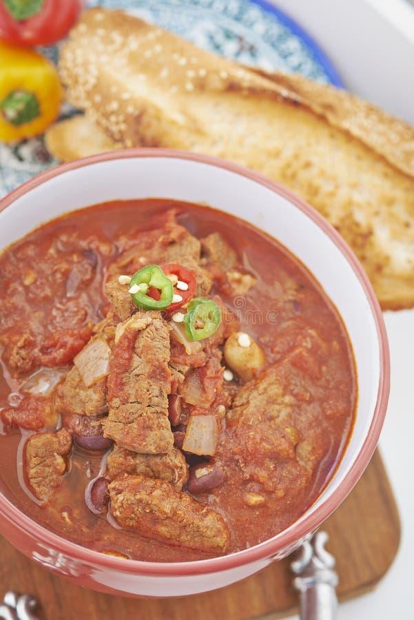 Nötkött- och tomatragu i bunke med rostat bröd royaltyfri fotografi