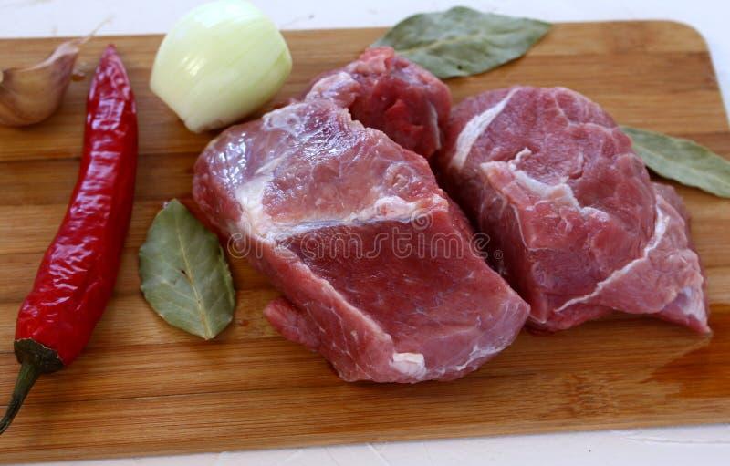 Nötkött på en skärbräda med grönsaker arkivfoton