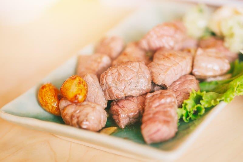 Nötköttbiff det saftiga lilla stycket blöter medelsällsynt för olje- kött med kryddor och grillade grönsaker royaltyfri fotografi