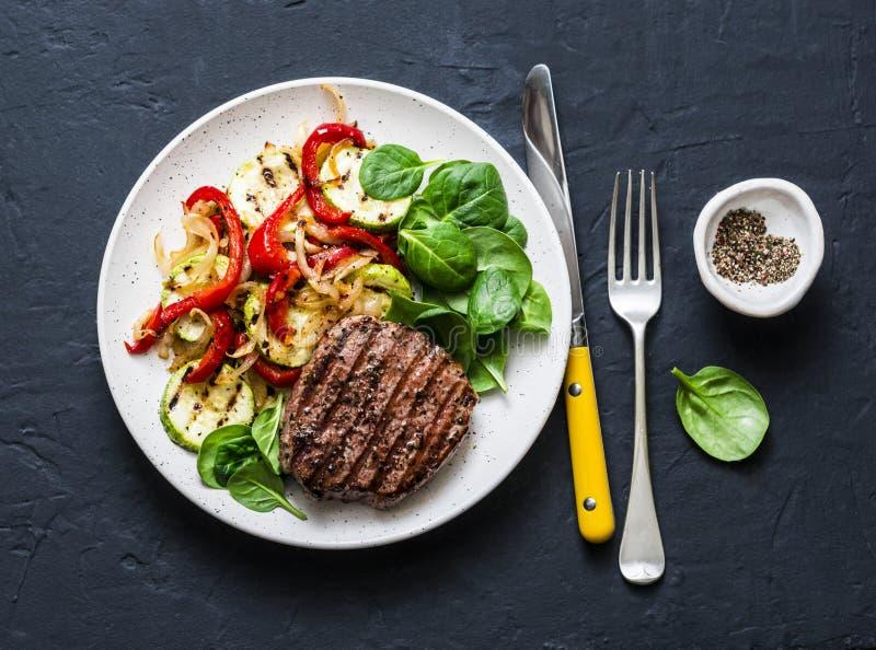 Nötköttbiff med grillade grönsaker, söt peppar, zucchinin och nya spenat på en mörk bakgrund Läckert sunt royaltyfri fotografi