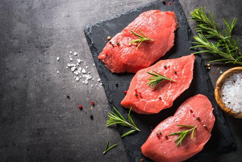 Nötköttbiff med rosmarin och kryddor på svart bakgrund royaltyfri fotografi
