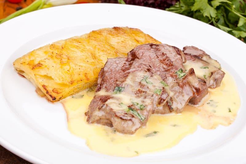 Nötköttfläskkarré med potatispajen på den vita plattan arkivfoto