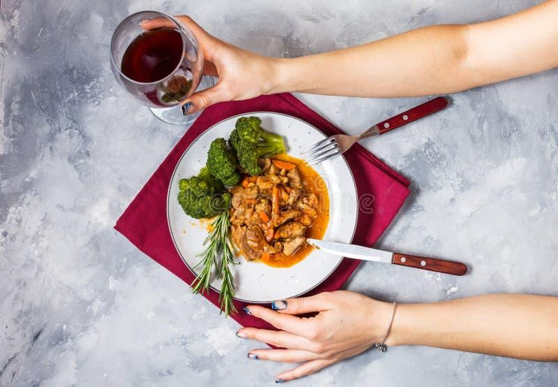Nötköttgulasch med grönsaker och broccoli på lantlig konkret bakgrund, händer för kvinna` s rymmer exponeringsglaset av vin royaltyfri foto