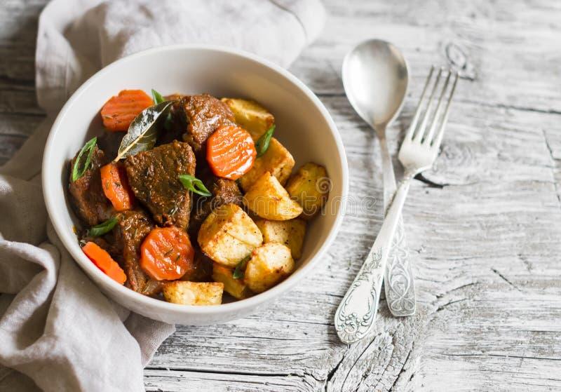 Nötköttgulasch med morötter och grillade potatisar i en vit bunke royaltyfri fotografi