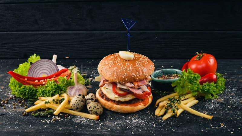 Nötkötthamburgare med vaktelägg och grönsaker arkivfoto