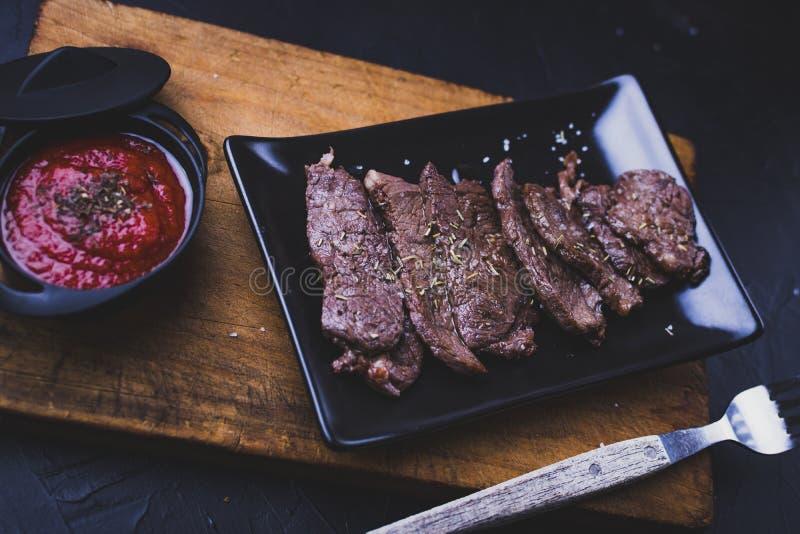 Nötköttsstek i remsor med tomatsås på trä royaltyfri bild