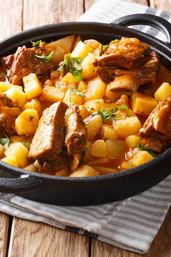 Nötköttstöd som låtas småkoka med potatisar och skynärbild i en kruka vertikalt arkivbild