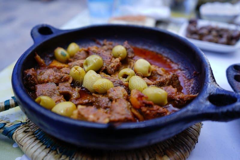Nötkötttajine med gröna oliv arkivfoto