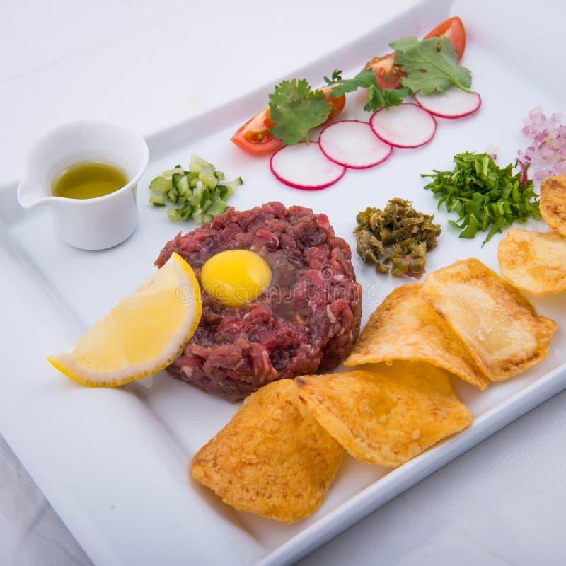 Nötkötttandsten med potatischiper och olivolja royaltyfri bild