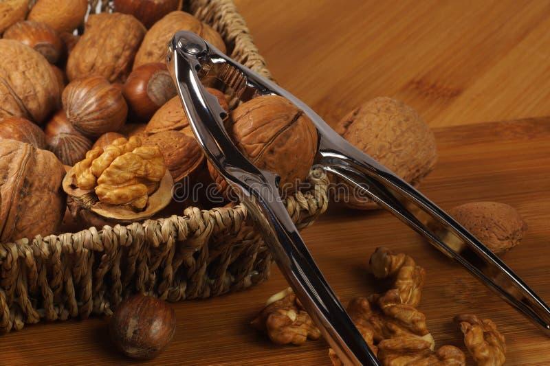 Nötknäppare som baseras på korgen Flätad korg som fylls med muttrar: valnötter, brasilian, hasselnötter och mandlar royaltyfri foto