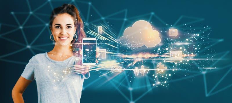 Núblese la computación con la mujer joven que sostiene hacia fuera un smartphone imágenes de archivo libres de regalías