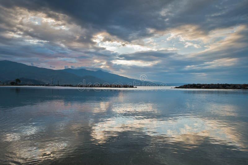 Núblese las reflexiones en un agua del Mar Egeo en la salida del sol, puerto de Volos con la montaña de Pelion en fondo fotos de archivo