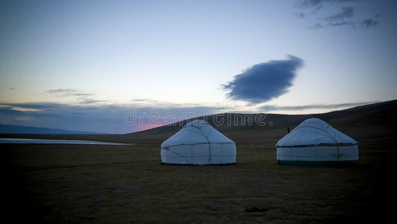 Núblese sobre los yurts en la orilla del lago en el amanecer, Kirguistán Kol de la canción foto de archivo