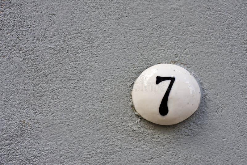 Número 7 em uma parede fotografia de stock