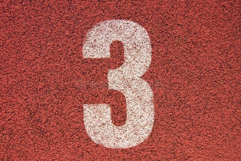 Número blanco en pista de goma roja, textura de la pista de pistas corrientes en pequeño estadio al aire libre imágenes de archivo libres de regalías