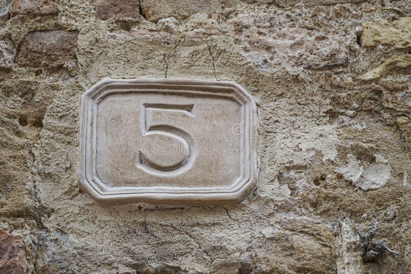 Número cinco en una pared imagen de archivo