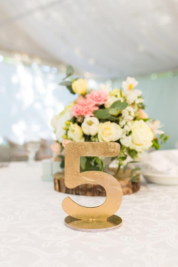 Número cinco na tabela para convidados no salão do casamento Número da tabela do casamento do ouro imagem de stock