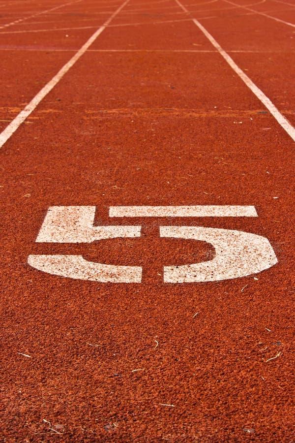 Número cinco no começo de uma pista de atletismo foto de stock