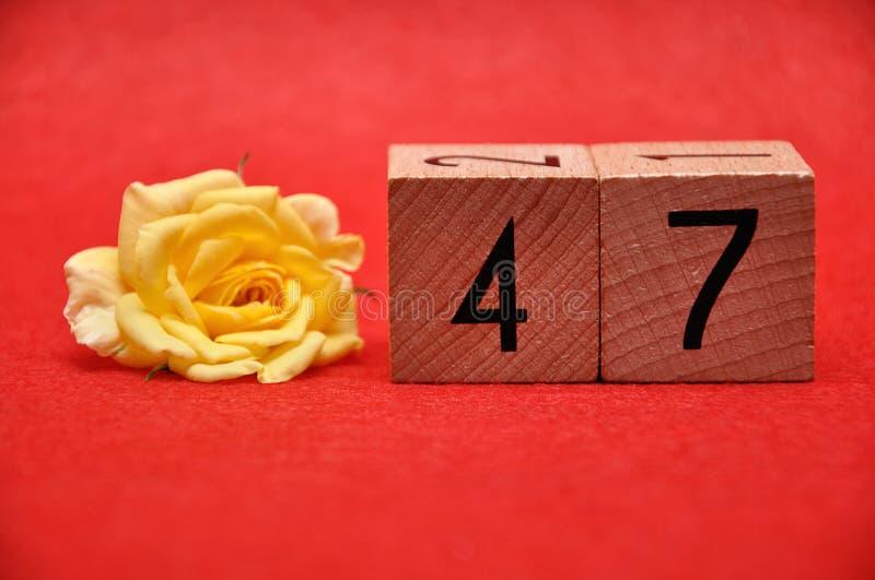 Número cuarenta y siete con una rosa amarilla imagenes de archivo