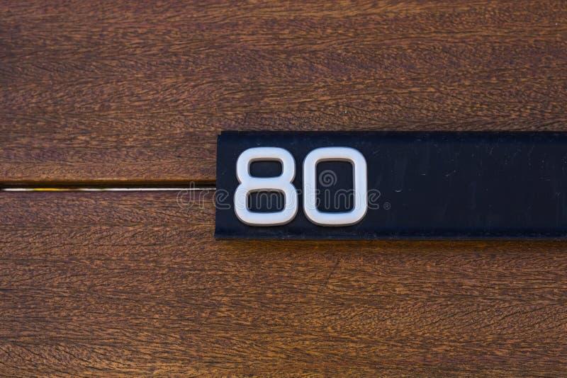 Número da casa oitenta no close-up de madeira da parede imagens de stock