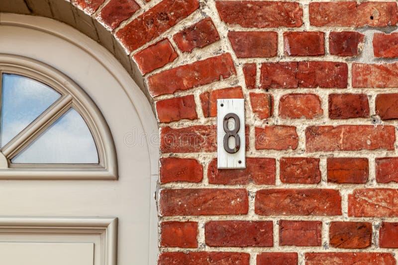 Número da casa oito 8 no metal moldado na madeira branca de Bélgica foto de stock