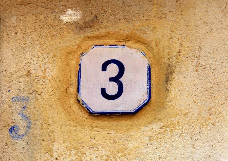 Número da casa resistido 3 três na parede de pedra velha fotos de stock