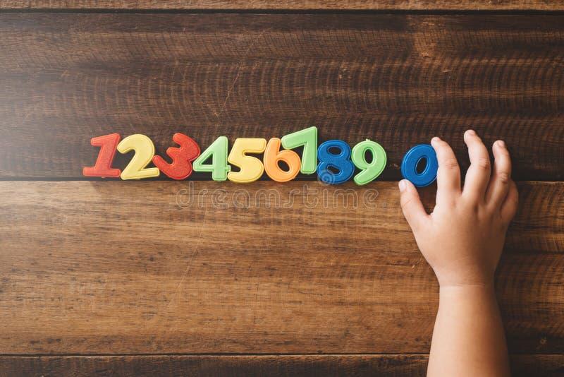 Número da terra arrendada da mão da criança zero com grupos do outro brinquedo plástico dos números coloridos em uma tabela de ma foto de stock
