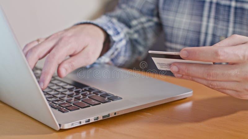 Número de cartão de crédito de datilografia do homem no laptop fotos de stock royalty free
