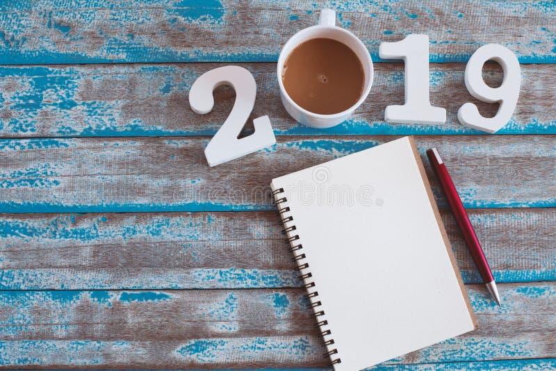 Número de madeira e café quente com texto 2019 e caderno foto de stock royalty free