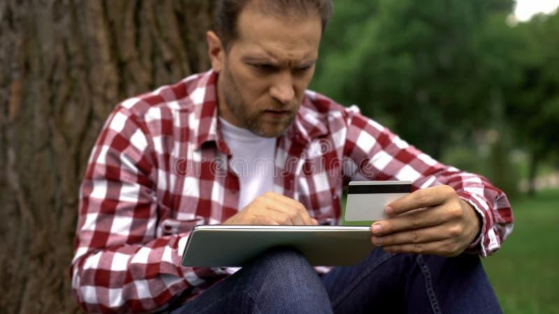 Número de tarjeta de crédito que entra del hombre en la tableta, pagando cuentas y multas que parquean en línea foto de archivo