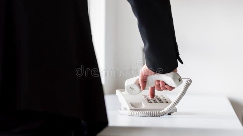 Número de telefone discado do homem de negócios em um landli branco clássico fotografia de stock