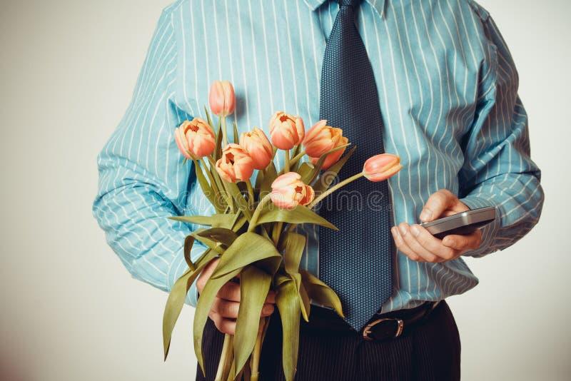 Número de telefone dos seletores do homem de negócios, guardando tulipas fotos de stock royalty free