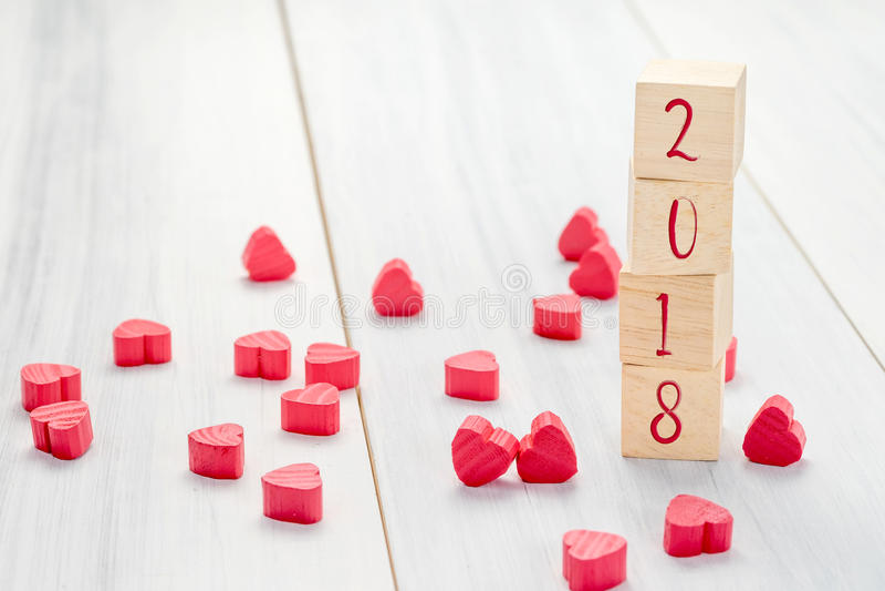 Número del Año Nuevo 2018 en el cubo de madera de la pila con el grupo del mini rojo h fotos de archivo libres de regalías