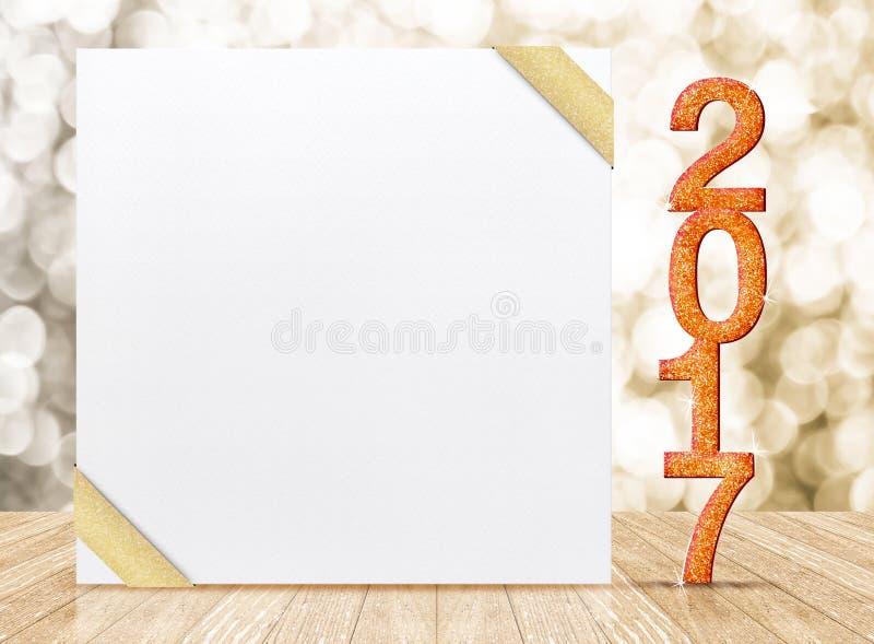 Número del brillo del Año Nuevo 2017 y tarjeta blanca con la cinta del oro adentro imagen de archivo