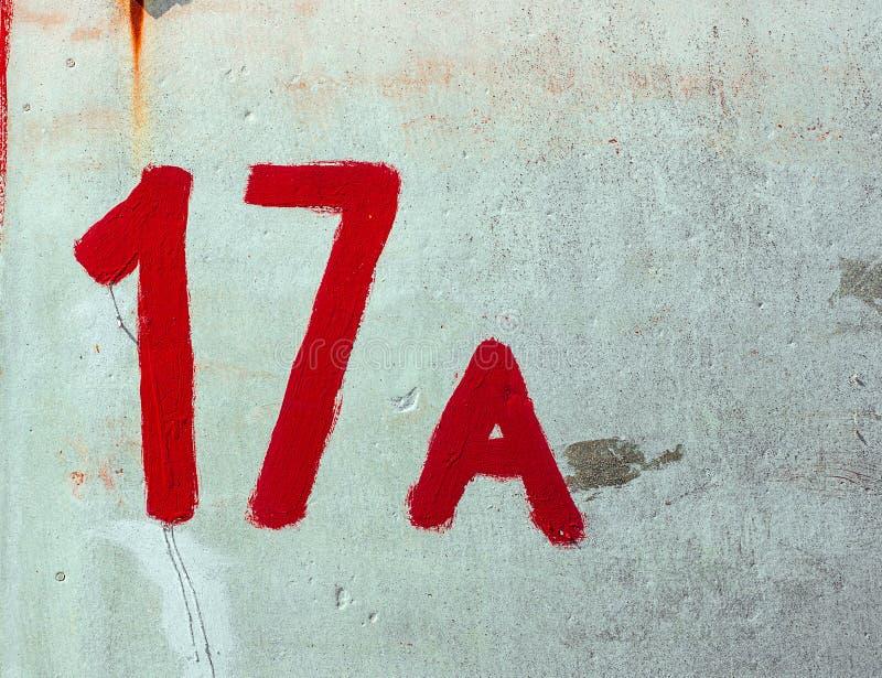 Número diecisiete A dibujado por la pintura roja en la pared Whitewashed Fachada lamentable del yeso del estante del ¡de With Dam foto de archivo libre de regalías