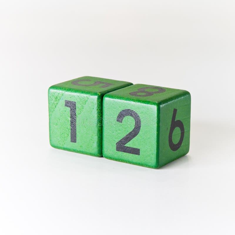 N?mero doce escrito en un cubo verde de madera en el fondo blanco imágenes de archivo libres de regalías