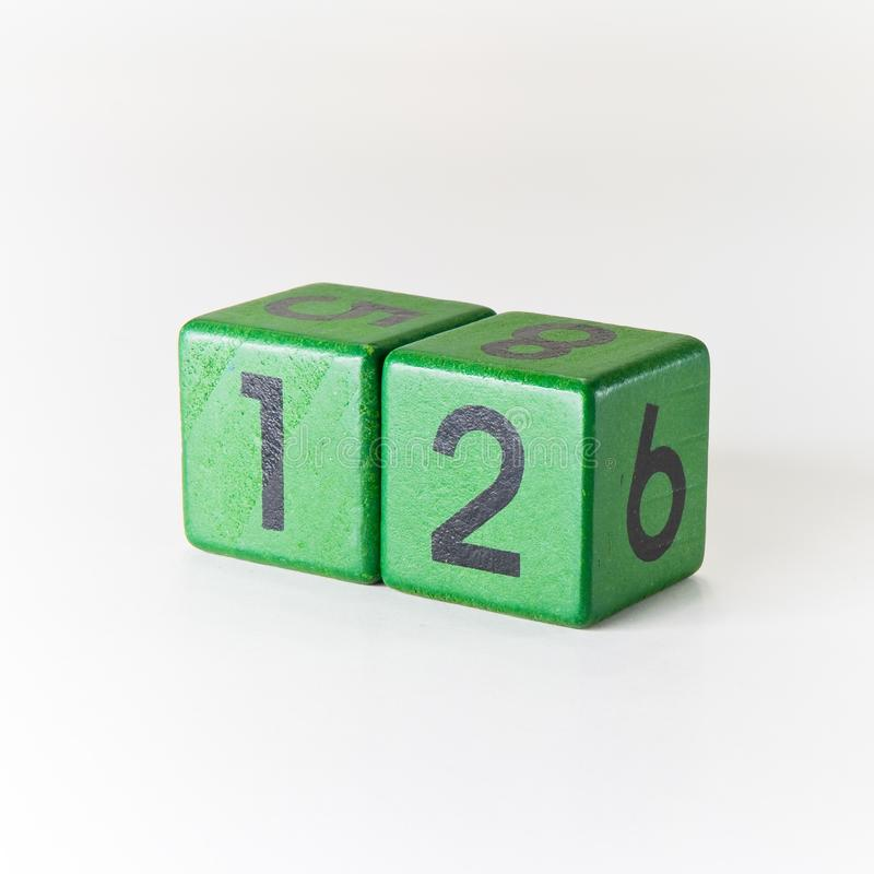 N?mero doze escrito em um cubo verde de madeira no fundo branco imagens de stock royalty free