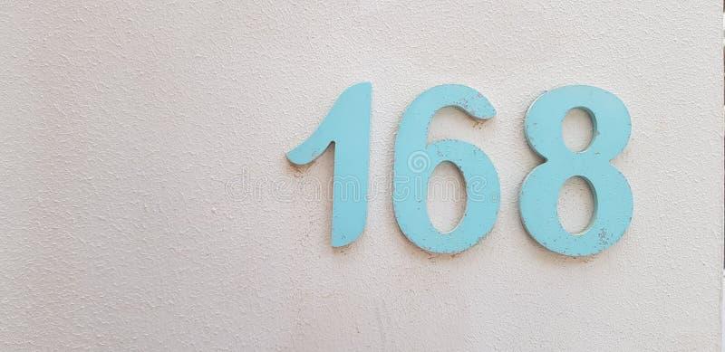 Número 168 en la pared pintada blanca imágenes de archivo libres de regalías