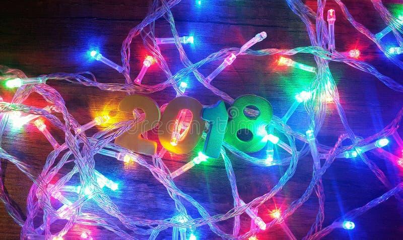 Número 2018 en las guirnaldas de las luces de la Navidad fotos de archivo