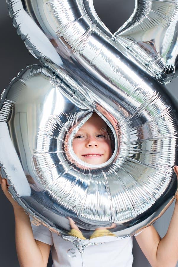 Número feliz del impulso del muchacho pared gris de 8 cumpleaños foto de archivo