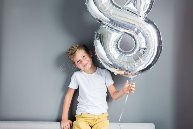 Número feliz del impulso del muchacho pared gris de 8 cumpleaños fotografía de archivo